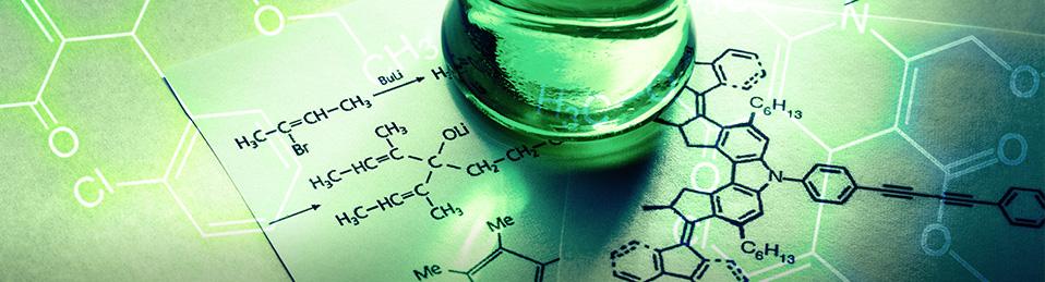 Imagen de un recipiente de cristal sobre un papel con fórmulas químicas