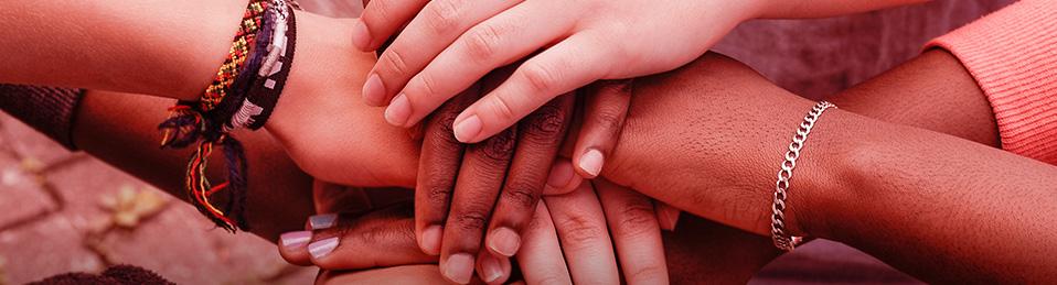 Fotograífa de manos de diferentes personas una sobre otra